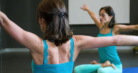Woman doing yoga exercise in studio 4k video. Girl sits lotus asana stretching Footage