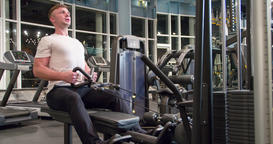 Man in gym pulls weight exercise 4k video. Training back muscles cable machine Footage