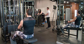 Fitness peoples in gym exercise 4k video. Man woman in weight training machine Footage