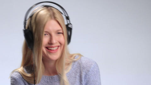 Blonde girl with headphones listening to music Footage