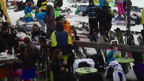 Panoramic view with a terrace where skiers sit on tables and tell and consume dr Live Action