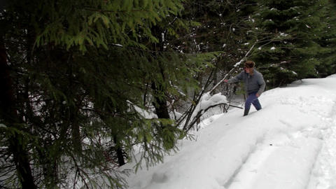 Forestry worker who goes on a road with snow through the forest and then down a  Footage