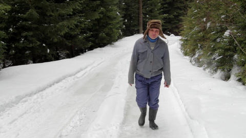 Forestry worker who goes on a road with snow through the forest 15 Live Action
