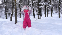 Small child dressed in pink overalls playing with snow in park covered with snow Footage