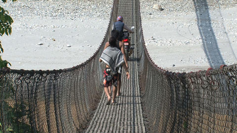People crossing a rope bridge in Nepal Stock Video Footage