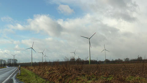 Seven rotating wind power generators in green landscape Footage
