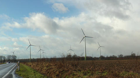 Seven rotating wind power generators in green landscape Stock Video Footage