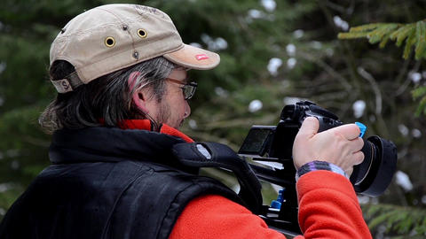 Cameraman filming with DSLR a movie that takes place in the fir forest during wi Footage