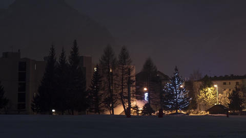 Zoom over snow covered buildings and trees lit by lamps and fog moving 12ap3 Footage