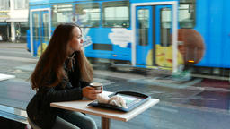 Young adult woman sit alone at casual restaurant, look out glass wall window Footage
