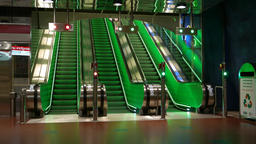 Empty moving stairway from lower ground, three escalators lit with green Footage