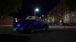 Blue Volkswagen cabriolet parked at night street, rear view, dark urban area Footage