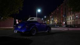 Blue Volkswagen cabriolet parked at night street, rear view, dark urban area Footage