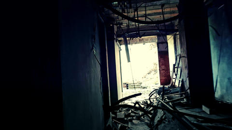 Wandering through dark hallways of abandoned factory towards light at end of glo Footage