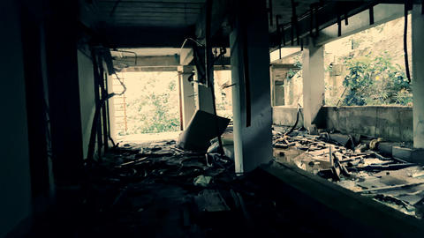 Shaky camera moves between gray concrete columns in destroyed abandoned building Footage