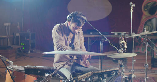 Young male drummer playing on electronic drum set in a studio