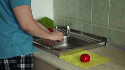 Man is washing vegetables in a sink Footage