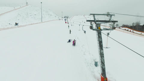 Aerial skiers and snowboarders go up the lift on the slope 画像