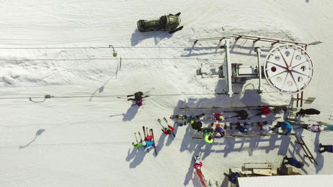 Aerial skiers and snowboarders go up the lift on the slope