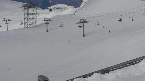 Plants chairlift cable and lift that runs on a piste where many skiers descend s Footage