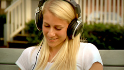 Pretty Woman Listens to Music in the Park on an iPad Stock Video Footage