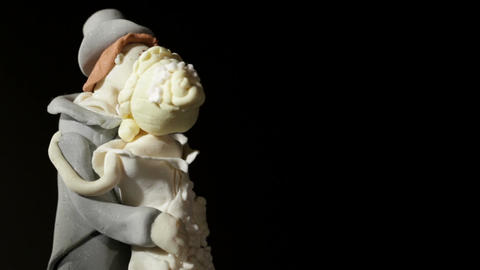 Wedding cake figurines rotating and kissing on black.... Stock Video Footage