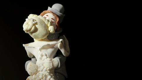 Wedding cake figurines rotating and kissing on black. Macro shot Footage