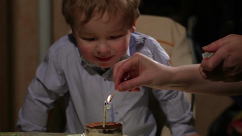 Kid's birthday. Boy blows out the candle in the tiramisu... Stock Video Footage