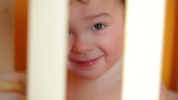 Portrait of the smiling little boy sitting in the playpen Stock Video Footage
