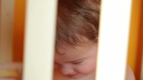 Portrait of the smiling little boy sitting in the playpen Footage