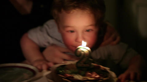 Kid's birthday. Boy blows out the candle with number 2 in... Stock Video Footage