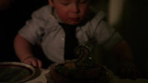 Kid's birthday. Boy blows out the candle with number 2 in the cake Footage