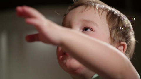 Two year old boy blowing soap bubbles Footage