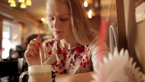 Portrait of girl enjoying coffee latte in cafe Stock Video Footage