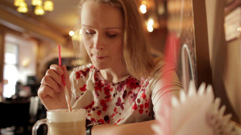 Portrait of girl enjoying coffee latte in cafe Stock Video Footage