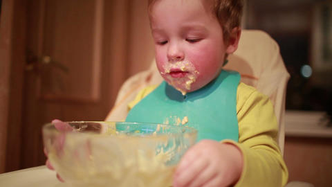 Two year old boy is having dinner and looking into the plate Footage