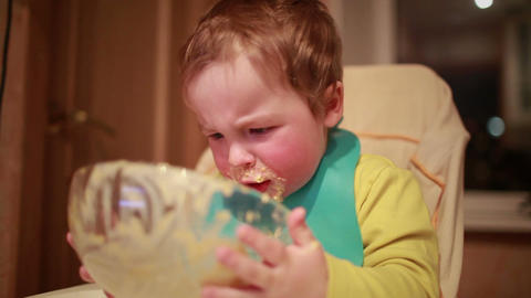 Two year old boy is having dinner and looking into the plate Stock Video Footage