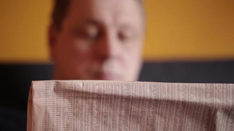 Middle-aged man reads financial news at home Stock Video Footage