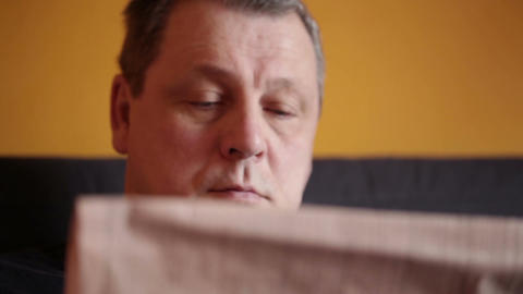 Middle-aged Man Reads Financial News At Home stock footage