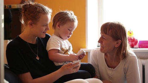 Two year-old boy plays with his mother and grandmother Stock Video Footage