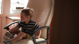Two year old boy is spinning on chair Stock Video Footage