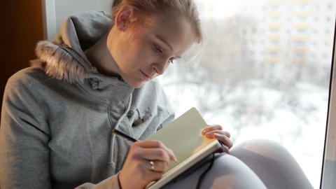 Young girl writing in her journal while sitting at a large window Footage
