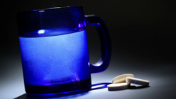 Tablet dissolving in a blue glass of water Stock Video Footage