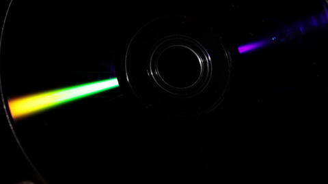 Refraction of light. Compact disk rotates in hand on a black background Footage