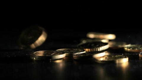Gold coins falling over dark background. Macro shot Stock Video Footage