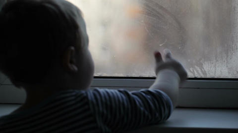 Little boy watching through the misted window Stock Video Footage