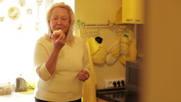 Senior woman eating apple in the yellow kitchen and looking to the camera Footage