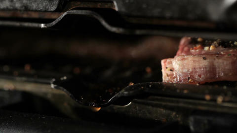 Pieces of meat are fried on the barbecue. Fat drops macro Footage