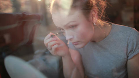 Through the window portrait of a beautiful girl applying... Stock Video Footage