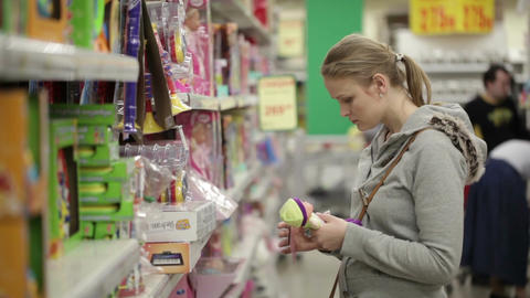Young woman is choosing toys for her kid. Middle shot... Stock Video Footage